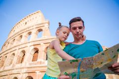 Family with map in front of Colosseum. Father and girl searching the attraction Stock Photos