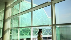 Girl standing at the window in airport terminal Stock Footage
