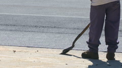 Asphalt Worker Scraping Ground with Shovel Stock Footage