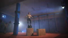 Strong man doing a box jump at the gym Stock Footage