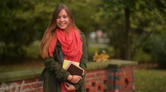 Excited happy student girl smiling joyful and blissful holding books outside in Stock Footage