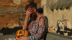 Bearded man holding a pumpkin and remove from the face Halloween makeup Stock Footage
