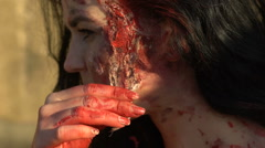 Girl removes from the face zombies makeup on Halloween on background of wall Arkistovideo