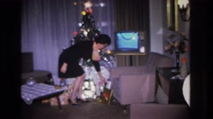 1966: a woman takes a seat on the couch and proceeds to open a christmas gift Stock Footage