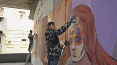 Two graffiti artists painting on the wall Stock Footage