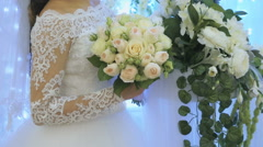 The bride standing next to arch of flowers indoors Stock Footage