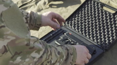The soldier pulls a gun out of the case and insert the pistol with ammunition Stock Footage