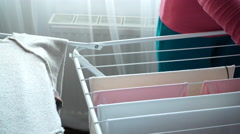 Woman hanging wet laundry clothes to dry on the rack dryer 4K Stock Footage