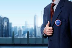 Man with black business suit with blue pinned button written 'VOTE' Stock Photos