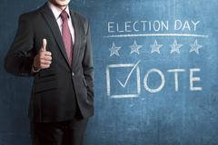 Man with business suit standing beside 'Election Day' Stock Photos