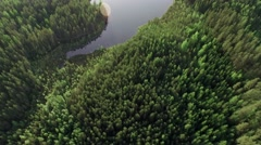 Aerial tilt shot of a natural small Nordic lake with golf course greens in the Stock Footage
