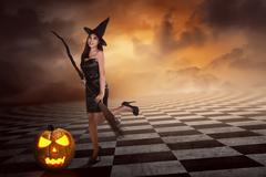 Pretty sexy young asian witch woman with a broom Stock Photos