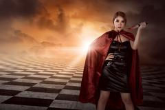 Witch woman with black costume wearing cloak hold knife Stock Photos