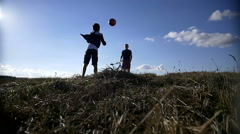 Two boys throw up the ball on top of the field, playing the ball Stock Footage