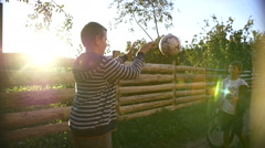 Two boys playing ball outdoors at sunset, throw ball with hands in farm Stock Footage
