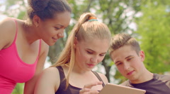 Friends using tablet. Group of multiracial friends having fun in nature Stock Footage