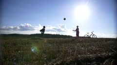 Two boys playing with a ball in the the field, throw up the ball Stock Footage
