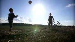 Two boys playing with a ball on top of the field, throw up the ball Stock Footage