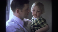 1968: father kissing irresistibly cute child he is holding in his arms  Stock Footage