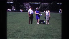 1968: three adults walking a black and white dog on a leash through grass  Stock Footage