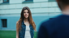 Happy smiling girl walking an the street and stopping in front of guy. Stock Footage