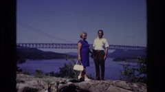 1968: couple standing in front of golden gate bridge with man sitting on rocks Stock Footage