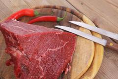 Beef meat chunk on wood with pepper Stock Photos