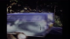 1968: a deer eating quietly on the edge of a road with vehicular traffic Stock Footage