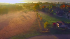 Tranquil idyllic Autumn neighborhoods shrouded in fog at dawn, aerial view. Stock Footage