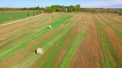 Flying low over big bails of hay in rustic Autumn farm field Stock Footage