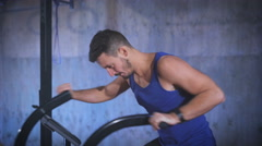 Fit young man using air bike for cardio workout at the gym Stock Footage