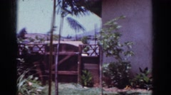 1962: span of backyard with fence, house with a window and a table  Stock Footage