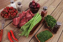 Fresh beef meat asparagus greenery spices cutlery wooden table pepper crushed Stock Photos