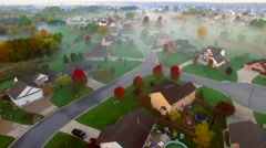 Tranquil idyllic Autumn neighborhood shrouded in fog at dawn Stock Footage