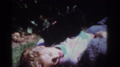 1962: an adolescent youth is resting as two puppies try to get his attention. Stock Footage