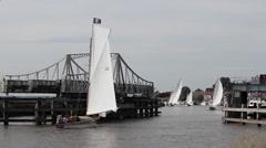 Sailing cruisers passing through Victorian swing bridge Stock Footage