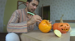 Man carving pumpkin for Helloween Stock Footage