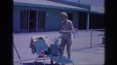 1963: woman wearing bathing suit puts object into her small pocketbook MEMPHIS Stock Footage