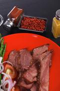 Roast beef meat slices on red plate Stock Photos
