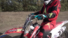 A Man Sitting on a Motorcycle in a Red Suit Stock Footage