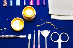 Tools for manicure, gel nail color yellow, messy shed foreman at the blue tab Stock Photos