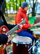 Male buskers on autumn outdoor play guitar. Stock Photos