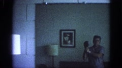 1963: man kneeling down bed holding something lamps portraits on walls different Stock Footage