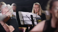 4K Orchestra during a performance, focus on oboist with violinists in foreground Stock Footage
