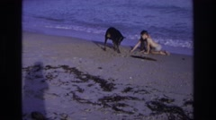 1968: a girl and a boy are playing in the sand by the ocean with a doberman Stock Footage