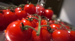 Slow motion of water flow  on cherry tomatoes Stock Footage