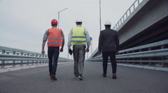 Construction engineers walking up a highway ramp Stock Footage