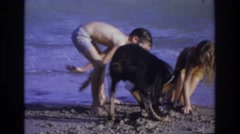 1968: kids and the dog loving their time at the beach playing in the sand OCEAN Stock Footage