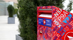 Woman placing mail in a canadian mail box with 4k resolution Stock Footage