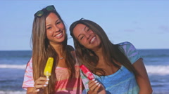 Twin Sisters Toasting With Melting Popsicles In The Summer At The Beach in Slow Stock Footage
